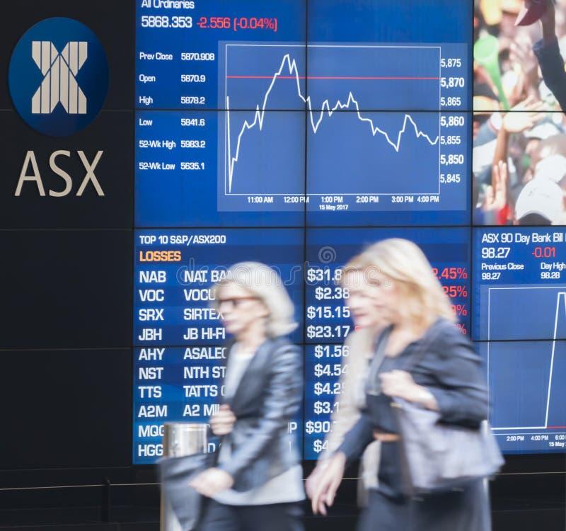La gente che cammina dopo il bordo della visualizzazione elettronica di Sydney Exchange Square fotografia stock libera da diritti