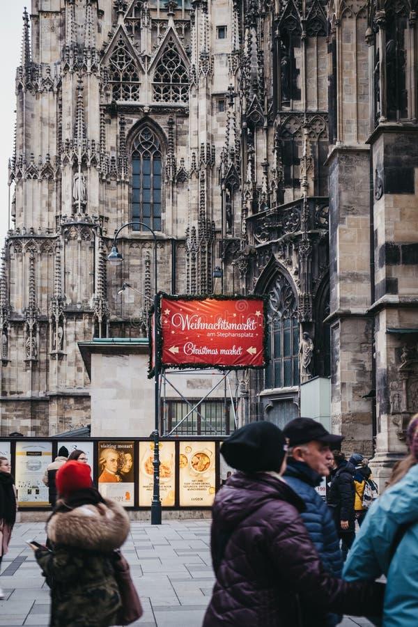 La gente che cammina dopo il segno direzionale alla stalla del mercato di Natale vicino alla st Stephen Cathedral, Vienna, Austri immagini stock