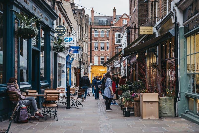 La gente che cammina fra i negozi sulla passeggiata della boccetta in Hampstead, Londra, Regno Unito fotografie stock