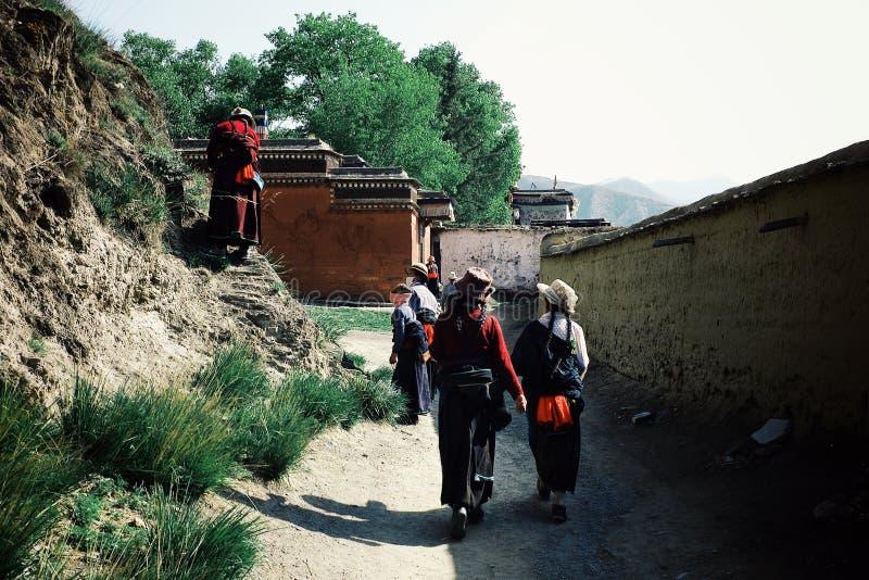 la gente che cammina intorno al monastero buddista tibetano come parte di un pellegrinaggio circonda in vestito tradizionale fotografia stock