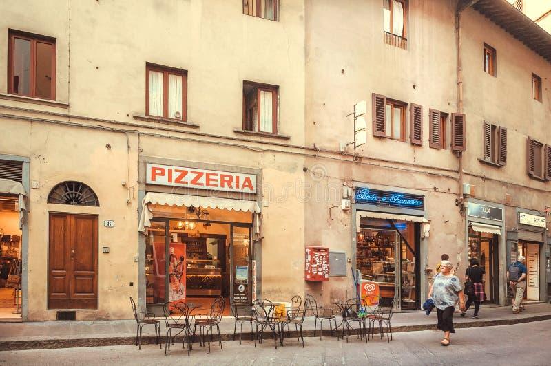 La gente che cammina intorno alla pizzeria in vecchia casa della città antica della Toscana fotografia stock