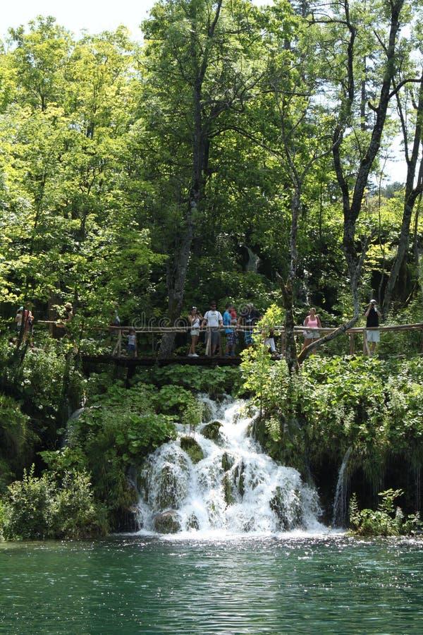 La gente che cammina su un percorso vicino ad una cascata fotografie stock libere da diritti