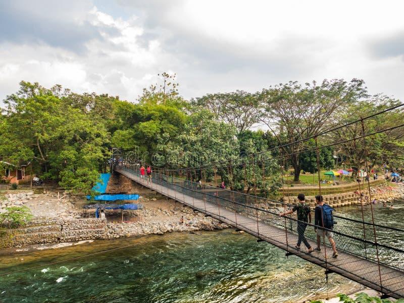 La gente che cammina sul ponte sospeso nel fiume di Bohorok, Bukit Lawang, Indonesia fotografia stock