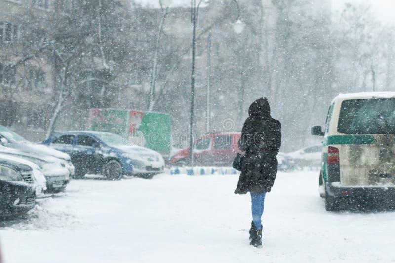 La gente che cammina tramite la via della città coperta di neve durante il heav fotografie stock