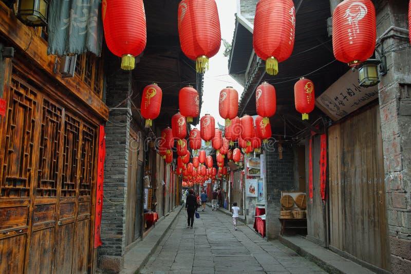 La gente che cammina in una via decorata piacevole in città antica di Fenghuang fotografia stock libera da diritti