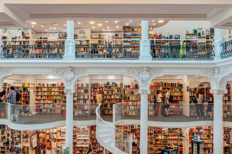 La gente che cerca un'ampia varietà di libri da vendere nel bello deposito di libro delle biblioteche fotografie stock