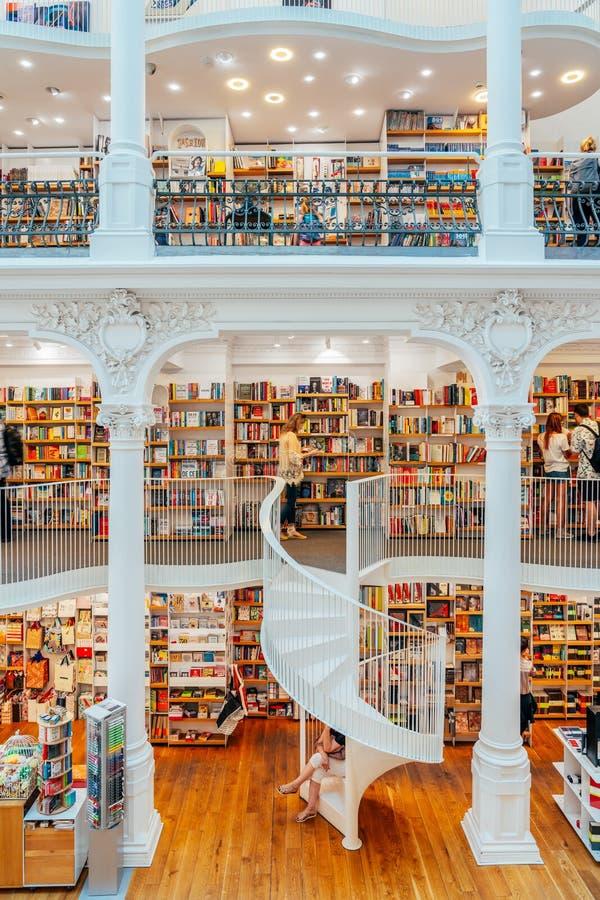 La gente che cerca un'ampia varietà di libri da vendere nel bello deposito di libro delle biblioteche fotografia stock libera da diritti