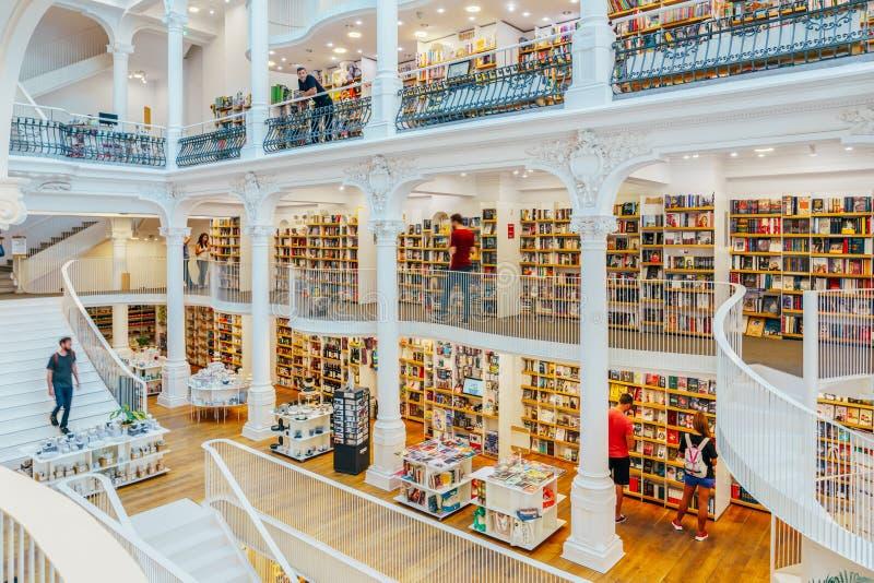 La gente che cerca un'ampia varietà di libri da vendere nel bello deposito di libro delle biblioteche immagini stock