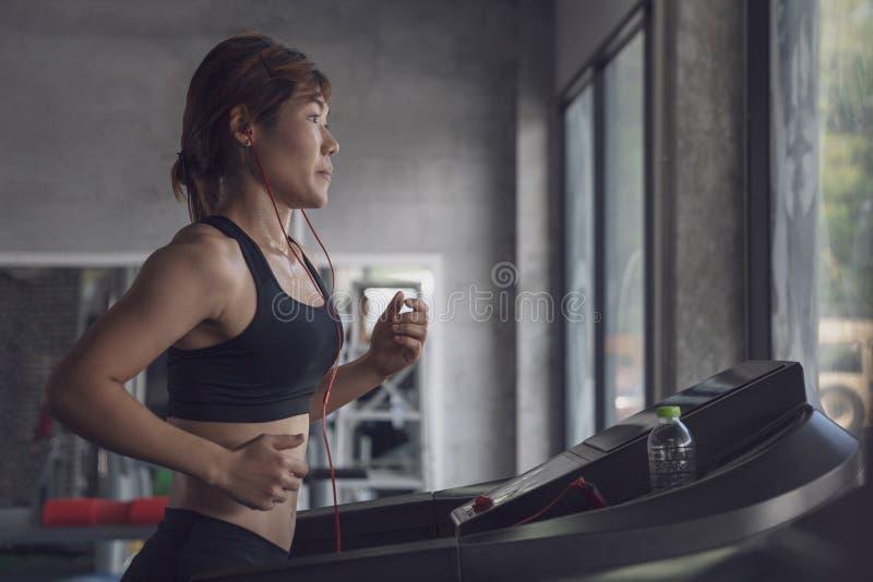 La gente che corre in pedana mobile della macchina alla palestra di forma fisica, allenamento della giovane donna nello stile di  immagine stock