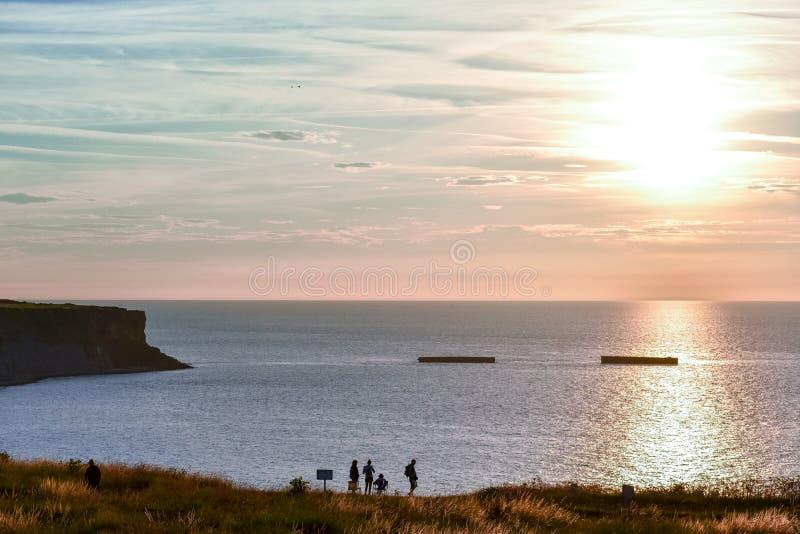 La gente che esamina il mare calmo con il cielo di tramonto Orizzonte variopinto sopra l'acqua e la parete atlantica La Normandia immagini stock