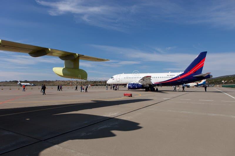 La gente che esamina il SuperJet 100-95 di Sukhoi degli aerei fotografia stock