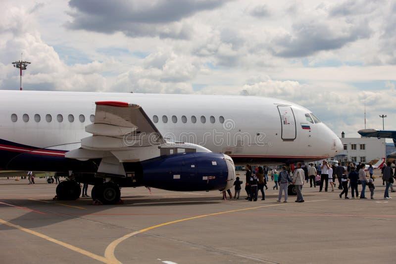 La gente che esamina il SuperJet 100-95 di Sukhoi degli aerei immagini stock libere da diritti