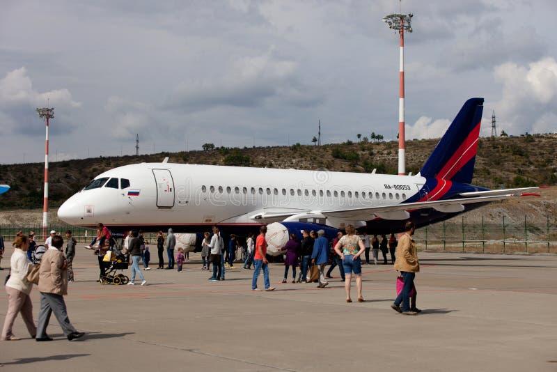 La gente che esamina il SuperJet 100-95 di Sukhoi degli aerei immagini stock