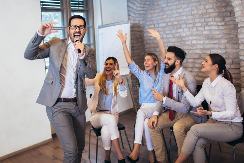 La gente che fa esercizio di allenamento del gruppo durante il karaoke di canto di seminario di team-building Attivit? dell'inter fotografia stock