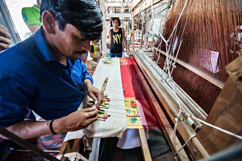 La gente che fa il tessuto variopinto del filato di seta dal telaio per tessitura indiano fotografie stock libere da diritti