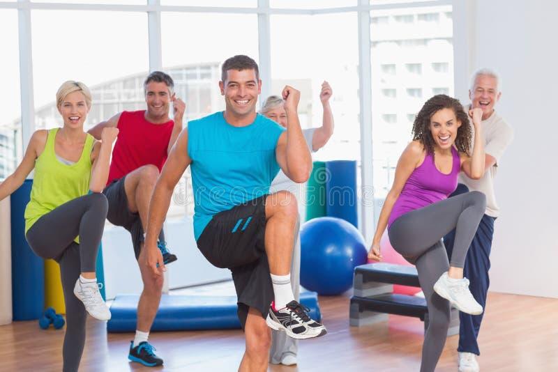 La gente che fa la forma fisica di potere si esercita alla classe di yoga immagini stock libere da diritti