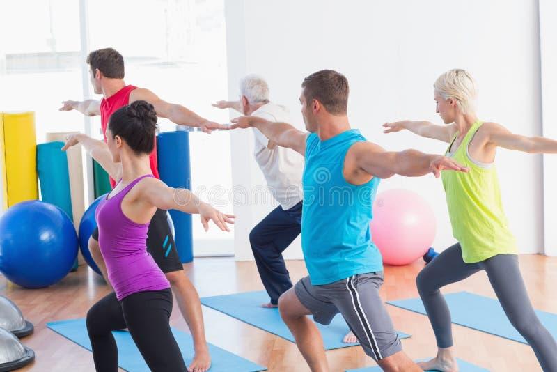 La gente che fa posa del guerriero nella classe di yoga immagine stock libera da diritti