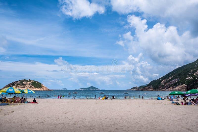 La gente che gode del sole splende alla spiaggia al pomeriggio soleggiato immagine stock libera da diritti