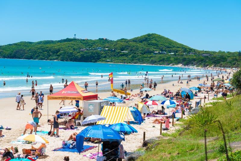 La gente che gode del tempo soleggiato sulla spiaggia a Byron Bay, NSW, Australia immagine stock libera da diritti