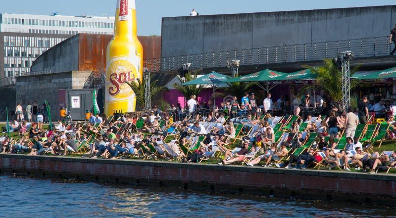 La gente che gode di un giorno caldo e soleggiato all'open bar sulla riva del fiume della baldoria del fiume immagine stock