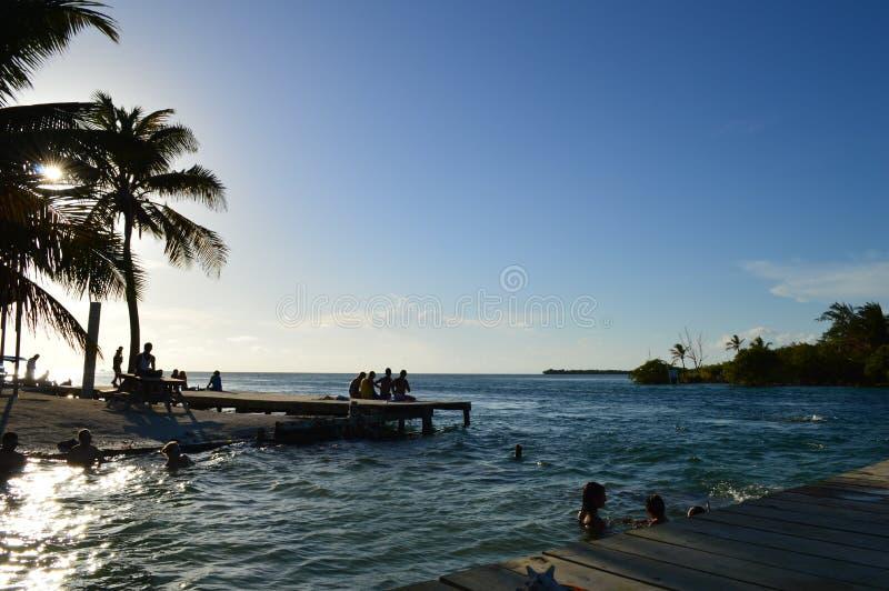 La gente che gode di un tramonto caraibico, spaccatura, calafato di Caye, Belize immagini stock