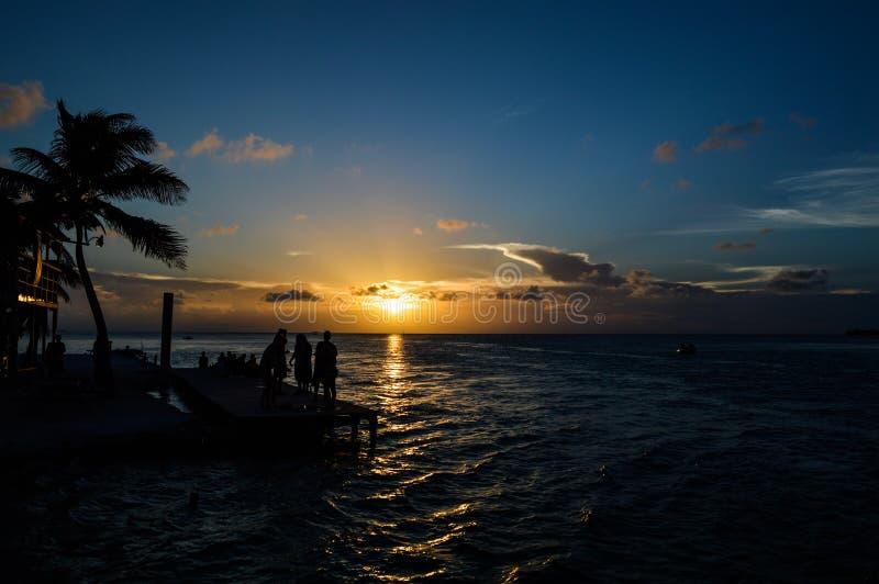 La gente che gode di un tramonto caraibico, spaccatura, calafato di Caye, Belize fotografia stock libera da diritti