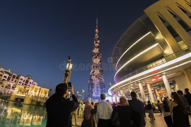 La gente che guarda Burj Khalifa dalla fontana del centro commerciale del Dubai fotografia stock libera da diritti