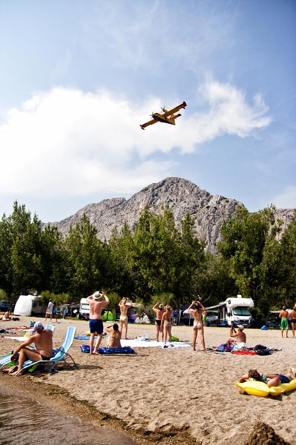 La gente che guarda e che fa le foto dell'aeroplano dei pompieri nell'azione fotografie stock