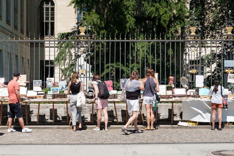 La gente che guarda susseguentemente i libri da vendere sul mercato delle pulci davanti all'università di Humboldt a Berlino immagini stock