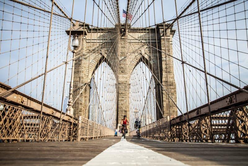 La gente che guida le loro bici sul ponte di Brooklyn fotografie stock
