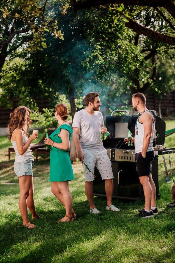 La gente che ha un partito della griglia del barbecue con le bevande, l'alimento e la cottura all'aperto Concetto di campeggio co immagini stock libere da diritti