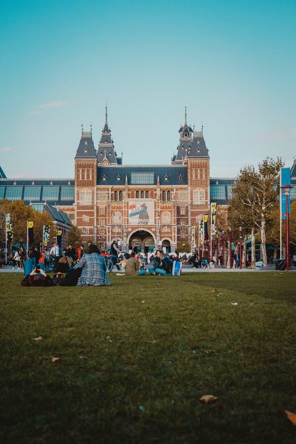 La gente che haniging fuori nel parco davanti a Rijksmuseum famoso a Amsterdam fotografia stock libera da diritti