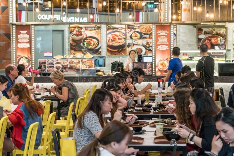 La gente che mangia alimenti a rapida preparazione su una corte di alimento negli Shoppes a Marina Bay Sands a Singapore fotografie stock