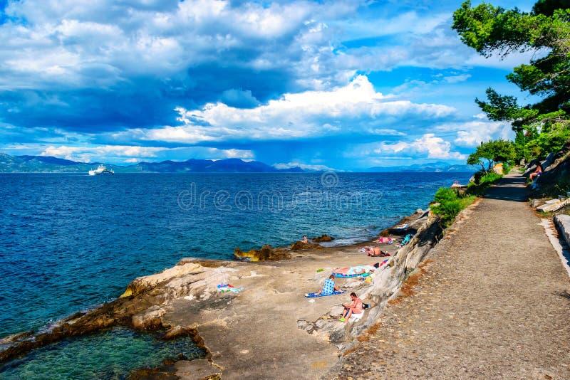 La gente che nuota e che prende il sole sulle rocce in Croazia del sud fotografia stock