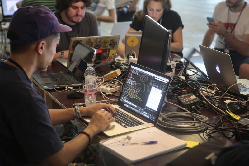 La gente che per mezzo dei computer portatili su area coworking immagine stock libera da diritti