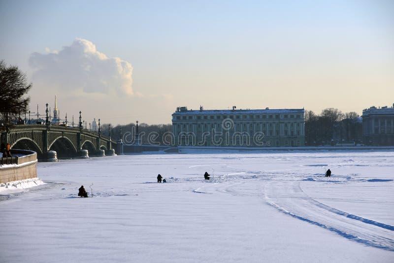 La gente che pesca su un fiume congelato di Neva nel centro urbano storico di St Petersburg immagini stock