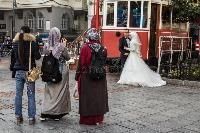 La gente che porta sciarpa islamica che prende recentemente le immagini di nozze con gli smartphones di una coppia sposata fotografia stock