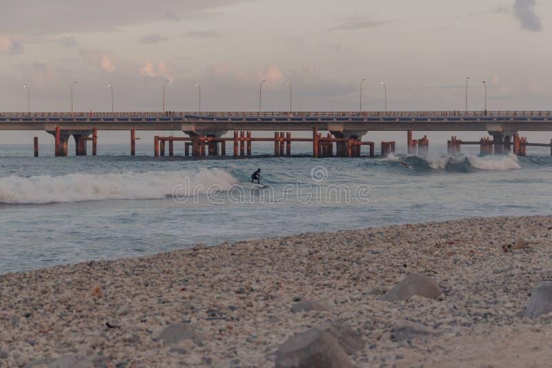 La gente che pratica il surfing in una piccola spiaggia in maschio, Maldive fotografie stock libere da diritti