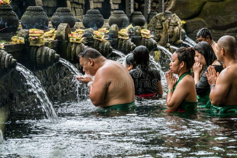 La gente che prega nell'acqua sorgiva santa del tempio di Pura Tirta Empul a Tampa, Bali, Indonesia fotografia stock libera da diritti