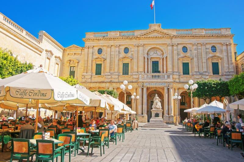 La gente che riposa in caffè dell'aria aperta alla Repubblica quadra La Valletta fotografia stock libera da diritti