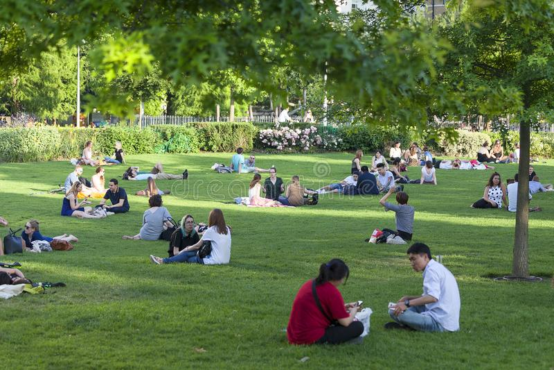 La gente che riposa sul prato inglese nel parco nel centro urbano, Londra, Regno Unito fotografia stock libera da diritti