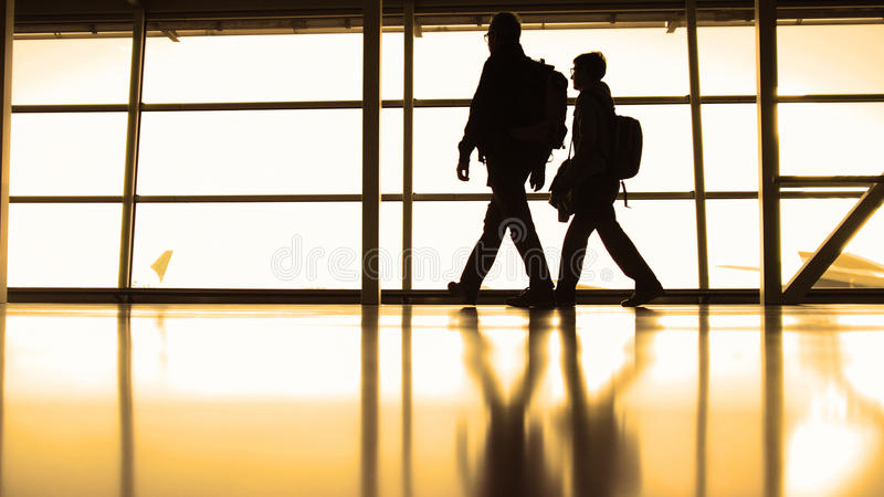 La gente che segue all'imbarco nel terminale di aeroporto davanti alla finestra, siluetta, calda immagine stock libera da diritti