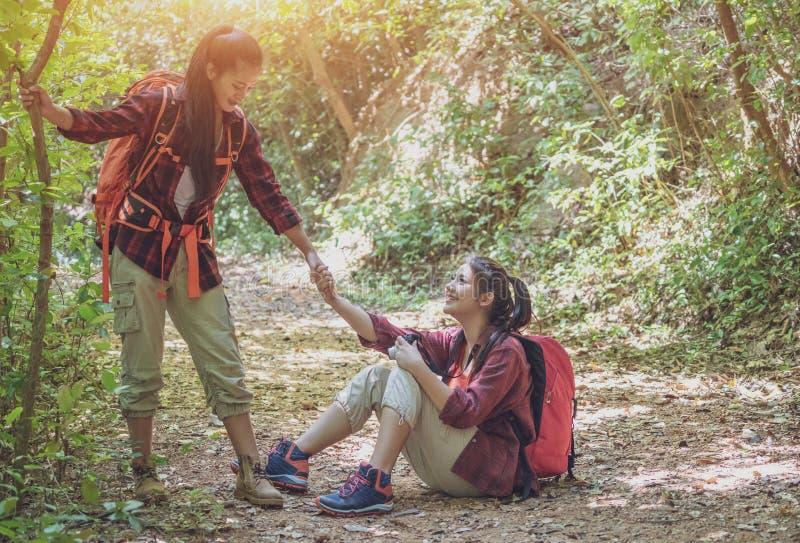 La gente che si aiuta a fare un'escursione su una montagna ad alba Dare una mano amica e concetto adatto di stile di vita dell'at immagine stock