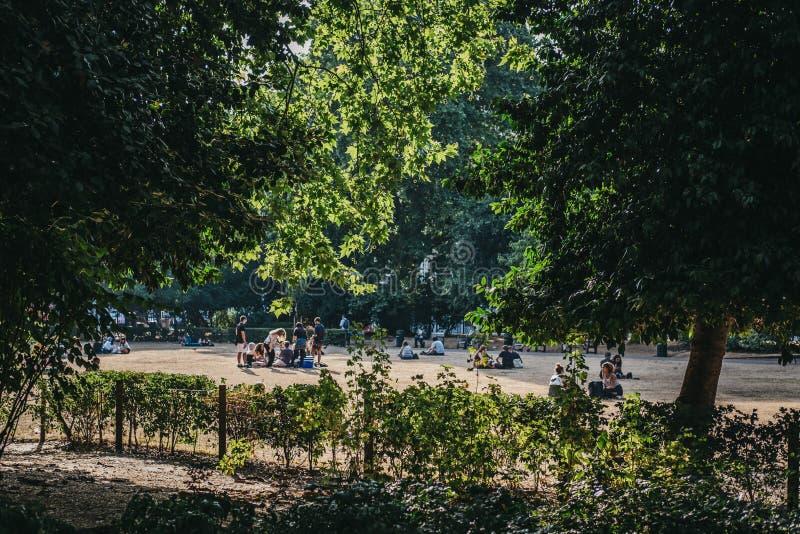 La gente che si rilassa nei campi della locanda di Lincoln durante l'onda di calore 2018 di estate a Londra, Regno Unito immagini stock libere da diritti