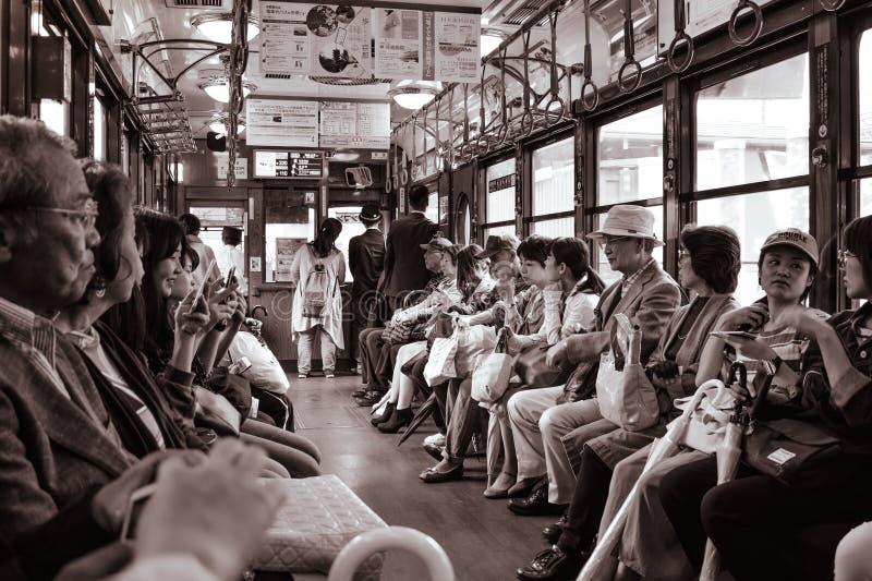 La gente che si siede in un treno di automobile storico della via a Kyoto immagini stock