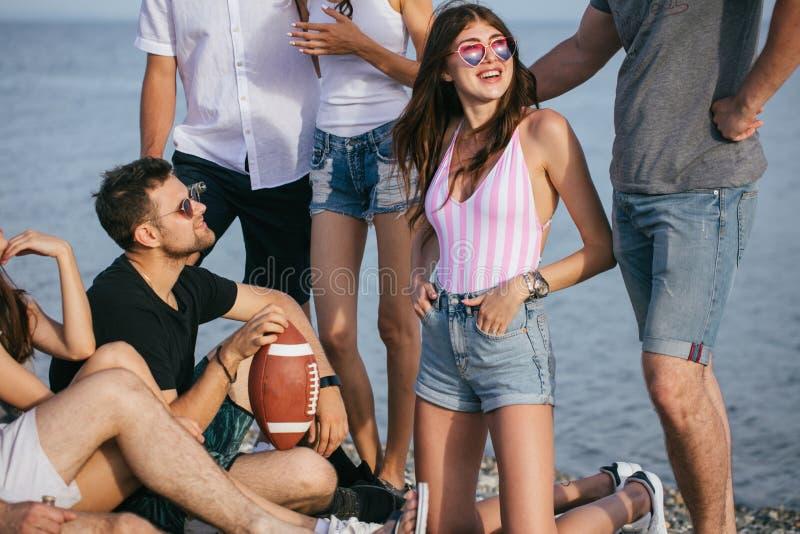 La gente che spende insieme tempo piacevole mentre sedendosi sulla birra divertiresi e di bevanda della spiaggia, fotografia stock libera da diritti