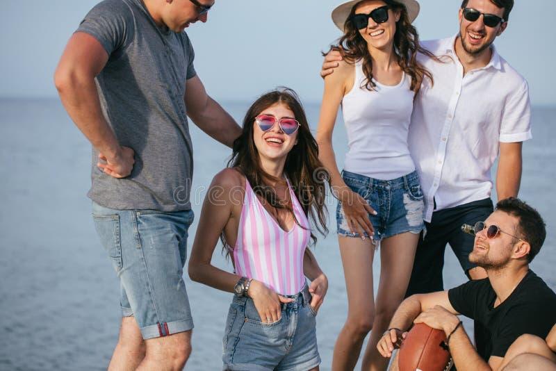 La gente che spende insieme tempo piacevole mentre sedendosi sulla birra divertiresi e di bevanda della spiaggia, fotografie stock libere da diritti