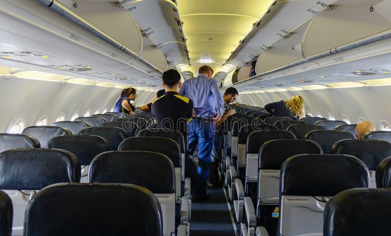 La gente che sta e che si siede in un aeroplano fotografie stock libere da diritti