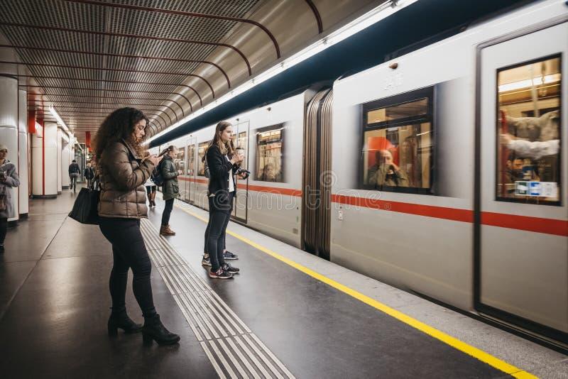La gente che sta sul binario sotterraneo a Vienna, Austria, treno che arriva, mosso immagini stock