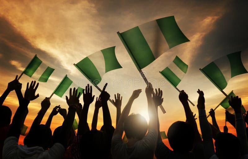 La gente che tiene bandiera della Nigeria in Lit posteriore fotografia stock libera da diritti